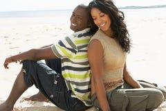 一起放松浪漫年轻人的海滩夫妇 免版税库存照片