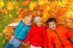 一起放置在秋叶的愉快的孩子 免版税库存照片