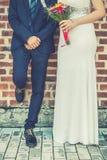 一起新娘和新郎在砖墙前面 免版税库存照片