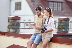 一起旅行愉快的年轻的夫妇 探索的城市地图在城市 免版税库存图片