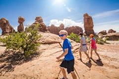 一起步行在拱门国家公园的美好的岩层的愉快的家庭 免版税库存图片