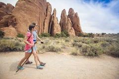 一起步行在拱门国家公园美丽的岩石峭壁的两个女孩  免版税库存图片