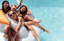 一起漂浮在水池的一个大可膨胀的玩具的妇女 免版税库存图片