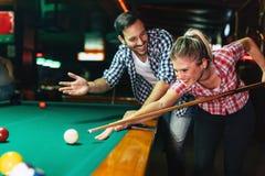 一起演奏落袋撞球的年轻夫妇在酒吧 库存图片