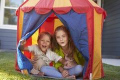 一起演奏里面帐篷的两个孩子在庭院里 免版税库存照片