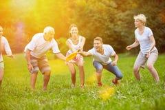 一起演奏飞碟的家庭在庭院里 库存照片