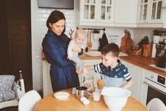一起烘烤在现代白色厨房里的愉快的家庭 烹调在舒适周末早晨的母亲、儿子和小女儿 免版税库存图片