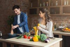 一起烹调健康晚餐的愉快的夫妇 免版税库存照片