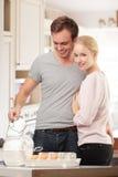 一起烹调在厨房里的年轻夫妇 库存照片