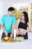 一起烹调新鲜的沙拉的夫妇 免版税库存图片