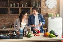 一起烹调晚餐的愉快的夫妇 免版税图库摄影