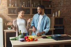 一起烹调晚餐的愉快的黑夫妇 免版税图库摄影