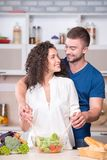 一起烹调晚餐的年轻夫妇在厨房里 库存照片