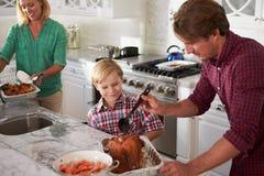 一起烹调烘烤土耳其的父亲和儿子在厨房里 免版税库存照片