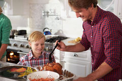 一起烹调烘烤土耳其的父亲和儿子在厨房里 图库摄影