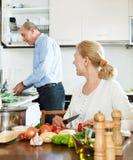 一起烹调爱恋的年长的夫妇做家事和 免版税图库摄影