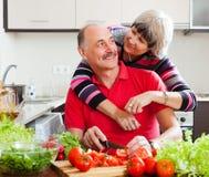 一起烹调爱恋的年长的夫妇 免版税库存图片