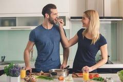 一起烹调膳食准备的年轻夫妇室内 图库摄影