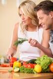 一起烹调食物的愉快的夫妇 库存图片