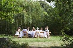 一起用餐在庭院里的愉快的家庭 库存照片