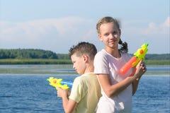一起男孩和女孩戏剧在有水枪的湖 免版税库存图片