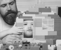 一起男孩和有胡子的人戏剧 父母身分概念 父亲和儿子做看通过建筑的门的鬼脸 库存照片