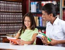 一起看书的图书管理员和女小学生 图库摄影