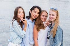 一起看照相机的四个最佳的女朋友 人们,生活方式,友谊,职业概念 年轻快乐的学生女孩 库存图片