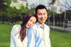 一起看照相机的美好的愉快的中国夫妇画象在公园 库存照片