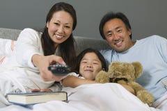 一起看电视的家庭在床上 库存图片