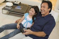 一起看电视的父亲和女儿在客厅大角度视图 库存照片