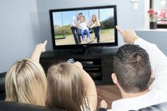 一起看电视的年轻家庭在家 免版税图库摄影