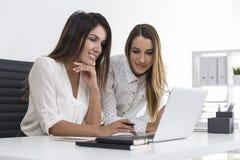 一起看膝上型计算机屏幕的两名女实业家 图库摄影