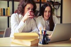 一起看膝上型计算机的两名妇女 免版税库存图片