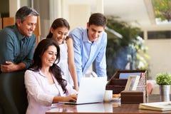 一起看膝上型计算机的家庭 免版税库存图片