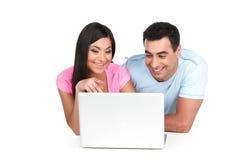 一起看膝上型计算机的微笑的印地安夫妇。 免版税图库摄影