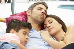一起睡觉在庭院吊床的家庭 免版税库存图片