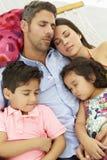 一起睡觉在庭院吊床的家庭 库存图片