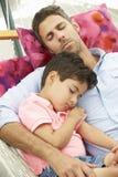 一起睡觉在庭院吊床的父亲和儿子 免版税库存图片