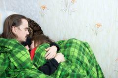 一起睡觉在扶手椅子的父亲和孩子 家庭休息 愉快的父母身分,父权 在毯子和女儿包裹的爸爸 免版税库存照片