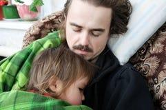 一起睡觉的父亲和的孩子在扶手椅子回家 家庭休息 愉快的父母身分,父权 爸爸和女儿 库存图片