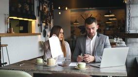 一起研究一个坚硬问题的男性和女性企业同事在咖啡馆 影视素材
