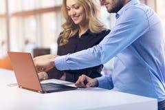 一起研究一台膝上型计算机的年轻夫妇在办公室 配合概念 图库摄影