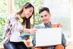 一起研究在的一台膝上型计算机的两名年轻亚裔雇员  免版税库存照片
