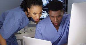 一起研究多台计算机的两位年轻医生 免版税图库摄影