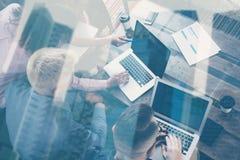 一起研究新的起始的项目的年轻工友在现代演播室 使用膝上型计算机的商人 被排行的办公室河摩天大楼 免版税库存照片