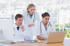 一起研究膝上型计算机和计算机的医护人员 免版税库存照片