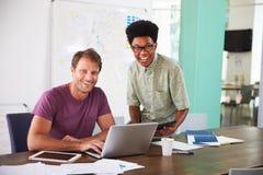 一起研究膝上型计算机的两个商人在办公室 免版税库存照片