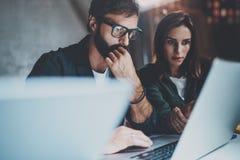 一起研究膝上型计算机的两个年轻工友在现代coworking的演播室在晚上 使用膝上型计算机的人佩带的玻璃 免版税库存照片
