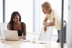 一起研究膝上型计算机的两名女实业家在会议室里 库存图片